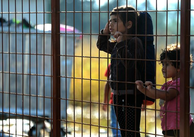 Children wait behind a fence to pass with their families in the southern Macedonian town of Gevgelija, Friday, Sept. 11, 2015.