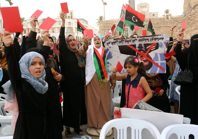 Libyan women raise red cards during a protest against the national unity government proposed by United Nations envoy Bernardino Leon on October 9, 2015 in Tripoli's central Martyrs Square.