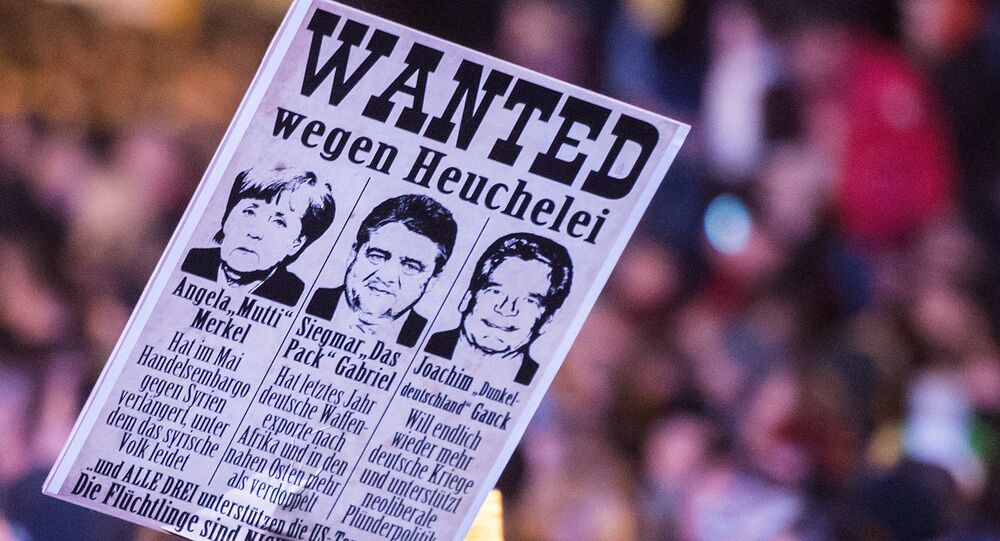Protestors hold a banner with manipulated images of German Chancellor Angela Merkel, German Economy Minister Sigmar Gabriel and German President Joachim Gauck, from left to right, during a demonstration of the PEGIDA (Patriotic Europeans against the Islamization of the West), marking the first anniversary of the anti-Islam group in Dresden, eastern Germany, Monday, Oct. 19, 2015.