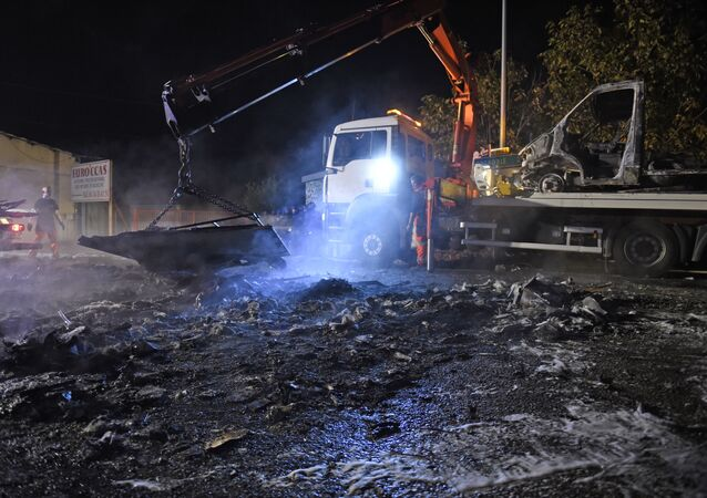 A man operates a crate, lifting up debris of burnt cars following a series of violent incidents on October 20, 2015 in Moirans, near Grenoble