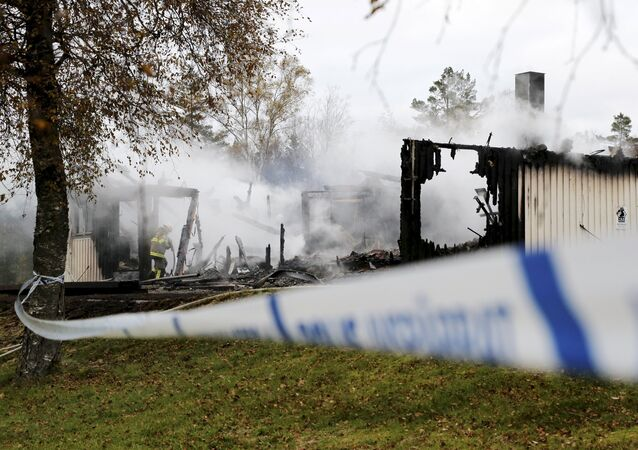 A firefighter works to extinguish a fire that broke out early in the morning at an accommodation for asylum seekers, near Munkedal in Sweden October 20, 2015