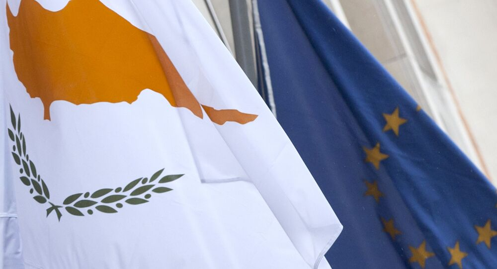 The Cypriot, left, and EU flag are seen at the Cypriot delegation building in Brussels on Sunday, March 24, 2013
