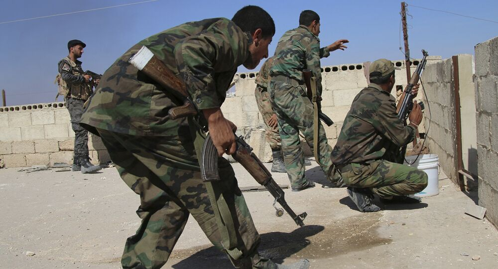 In this photo taken on Sunday, Oct. 11, 2015, Syrian soldiers fire repelling an attack in Achan, Hama province, Syria