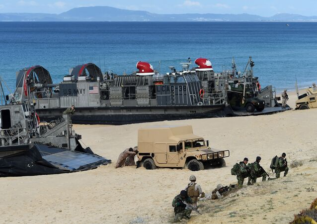 US marines push a Humvee stuck on the sand as they disembark from the overcrafts deploid by the USS Arlington amphibious transport dock during the NATO's Trident Juncture exercise at Pinheiro da Cruz beach, south of Lisbon, near Grandola on October 20, 2015