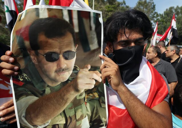 A Syrian who lives in Lebanon holds a photo of Syrian President Bashar Assad, during a rally to thank Moscow for its intervention in Syria, in front of the Russian embassy in Beirut, Lebanon, Sunday, Oct. 18, 2015