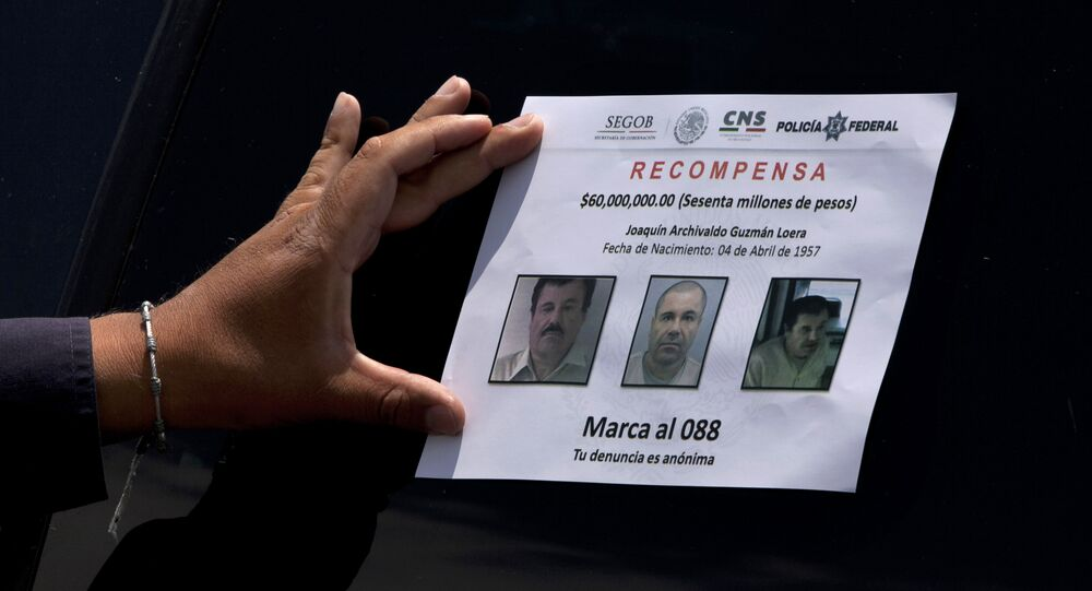 A Federal Police presses on a reward notice for information leading to the capture of drug lord Joaquin El Chapo Guzman, who made his escape from the Altiplano maximum security prison via an underground tunnel, in Almoloya, west of Mexico City, Thursday, July 16, 2015