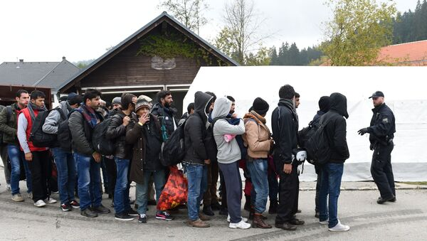 German police officer instructs migrants ahead of their walk from the Austrian-German border to a first registration point of the German federal police in the small Bavarian village Wegscheid, southern Germany, on October 20, 2015 - Sputnik International