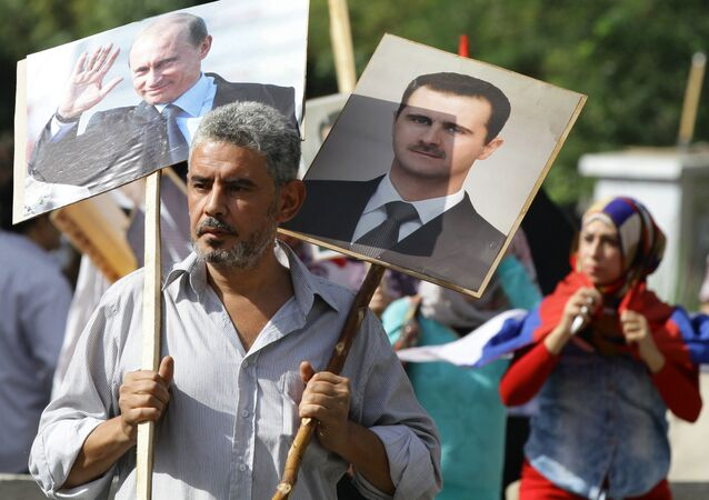 A Syrian man holding up portraits of President Bashar al-Assad and his Russian counterpart Valdimir Putin (L) joins several hundred people who gathered near the Russian embassy in Damascus on October 13, 2015