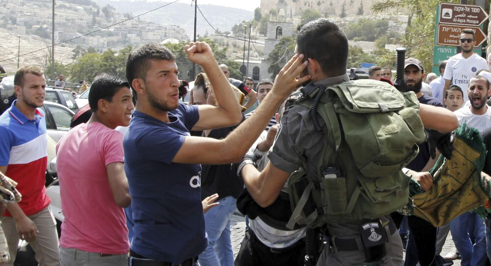 An Israeli border policeman exchanges blows with a Palestinian man during a confrontation after Friday prayers outside the Old City in Jerusalem Friday, Oct. 2, 2015
