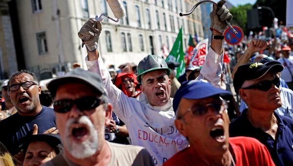 People shout slogans outside the Portuguese parliament during a protest by Portugal's main union CGTP, General Confederation of the Portuguese Workers, against cuts in salaries and pensions and others austerity measures taken by the government, in Lisbon, Thursday, July 10, 2014. - Sputnik International