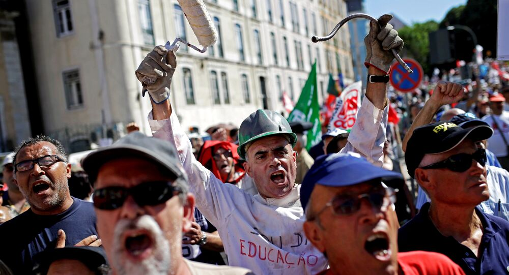 People shout slogans outside the Portuguese parliament during a protest by Portugal's main union CGTP, General Confederation of the Portuguese Workers, against cuts in salaries and pensions and others austerity measures taken by the government, in Lisbon, Thursday, July 10, 2014.