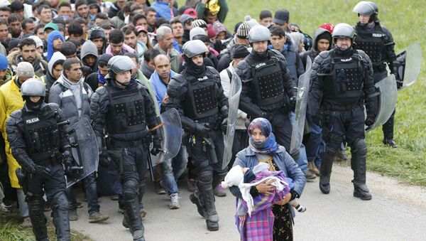 Police officers escort Fatima from Syria (front) and other migrants as they make their way on foot after crossing the Croatian-Slovenian border, in Rigonce, Slovenia, October 22, 2015 - Sputnik International