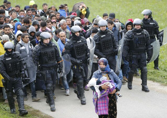 Police officers escort Fatima from Syria (front) and other migrants as they make their way on foot after crossing the Croatian-Slovenian border, in Rigonce, Slovenia, October 22, 2015