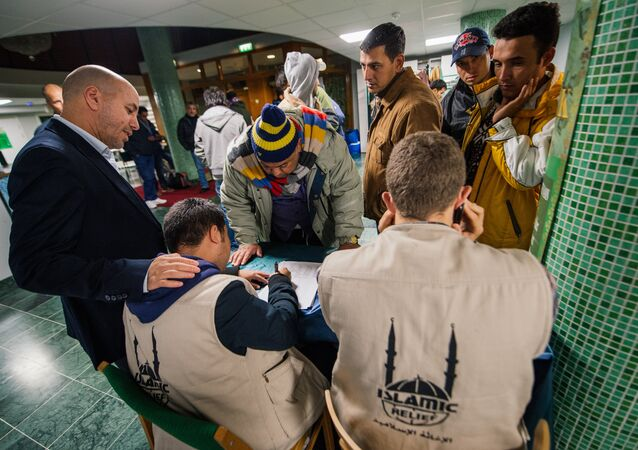 Abdallah Salah (L), President of Islamic Relief Sweden, helps refugee's as they register their names upon arrival to Stockholm central mosque on October 15, 2015 after many hours bus journey from the southern city of Malmo