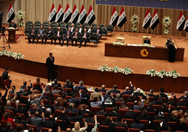 Iraqi lawmakers raise their hands to approve a new government in Baghdad, Iraq, Monday, Sept. 8, 2014