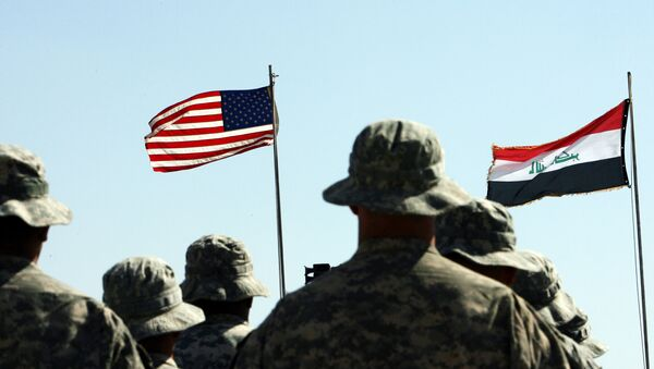 US troops stand to attention in front of American and Iraqi (R) flags during a handover ceremony near the northern Iraqi town of Hawija - Sputnik International