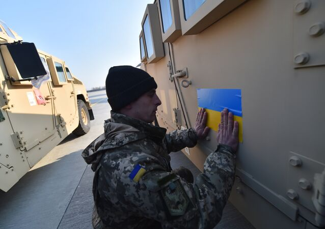 An Ukrainian serviceman sticks an Ukrainian flag on a Humvee at Kiev airport on March 25, 2015 during a welcoming ceremony of the first US plane delivery of non-lethal aid, including 10 Humvee vehicles
