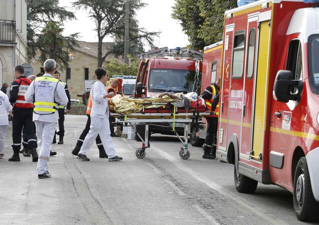 Rescue workers carry a injured person on a stretcher during rescue operations near the site where a coach carrying members of an elderly people's club collided with a truck outside Puisseguin near Bordeaux, western France, October 23, 2015