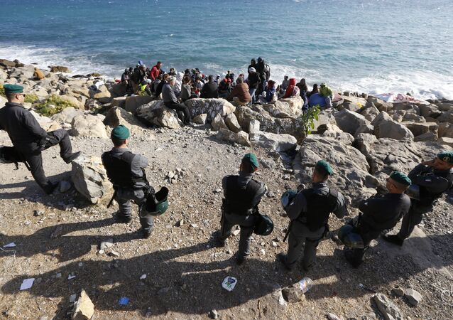 Migrants wait on the rocks on the shoreline under the surveillance of policemen on September 30, 2015 at the French-Italian border in Ventimiglia