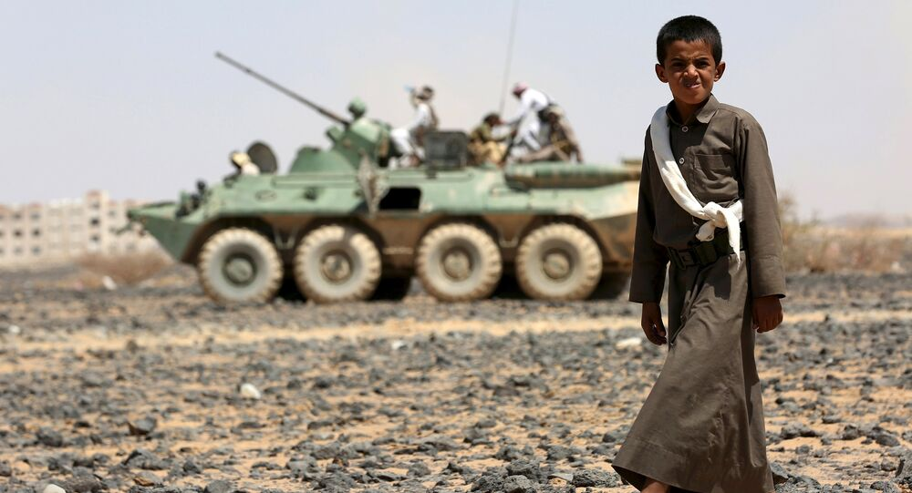 A boy walks in front of fighters of the Popular Resistance Committees riding on an armored vehicle during a ceremony where they formally take over territory that the government had managed to recover from Houthi militants, in the central province of Marib October 11, 2015.