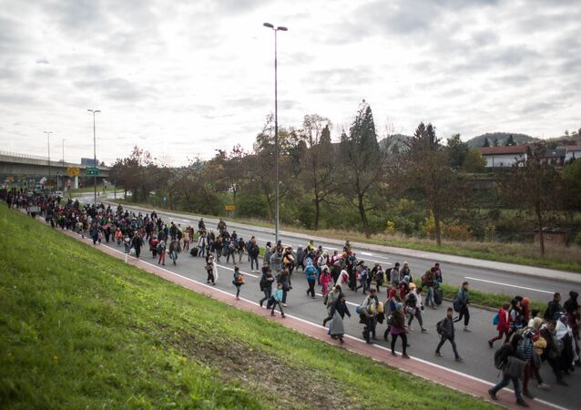 Refugees and migrants walk on a road as they leave Sentilj, Slovenia, on their way to cross the Slovenian-Austrian border on October 23, 2015