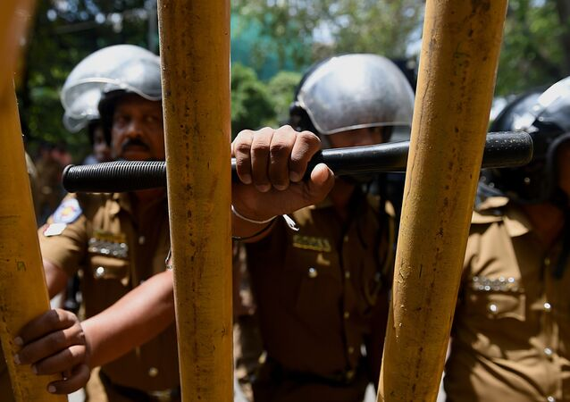Sri Lankan police watch as Tamil protesters hold placards demanding the release of activists being held under tough anti-terror laws in the Sri Lankan capital Colombo on October 14, 2015