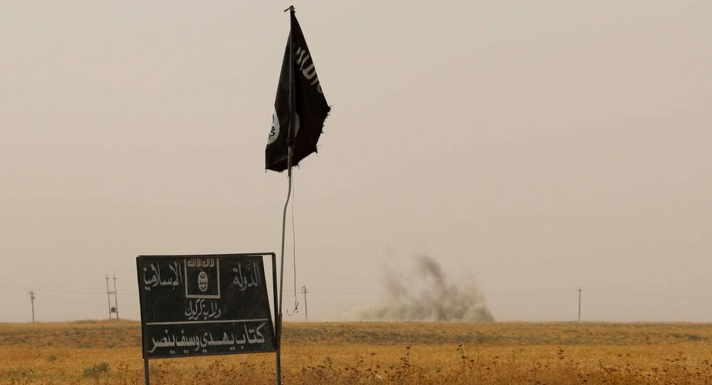 (FILES) A file picture taken on September 11, 2015, shows smoke rising in the distance behind an Islamic State (IS) group flag and banner after Iraqi Kurdish Peshmerga fighters reportedly captured several villages from IS group jihadists in the district of Daquq, south of the northern Iraqi multi-ethnic city of Kirkuk