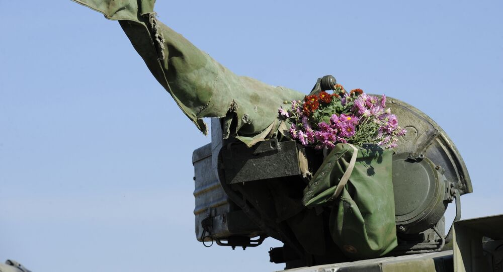 A tank of the Ukrainian forces, with flowers hung on its turret, rides from the front line near the village of Crymske in the Lugansk region on October 5, 2015