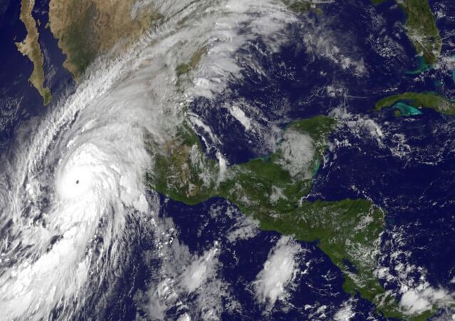 This satellite image taken at 10 a.m.. EDT on Friday, Oct. 23, 2015, and released by the National Oceanic and Atmospheric Administration shows Hurricane Patricia, left, moving over Mexico's Pacific Coast.