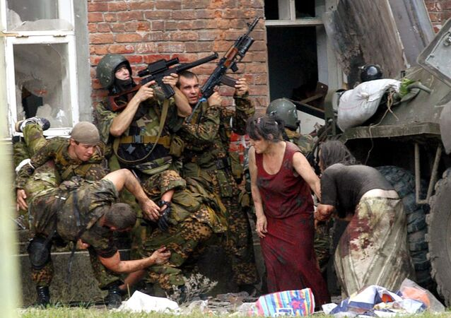A Russian special police soldier (L) carries an injured colleague as two soldiers and two women take cover behind the APC during the rescue operation of Beslan's school, northern Ossetia, September 3,2004