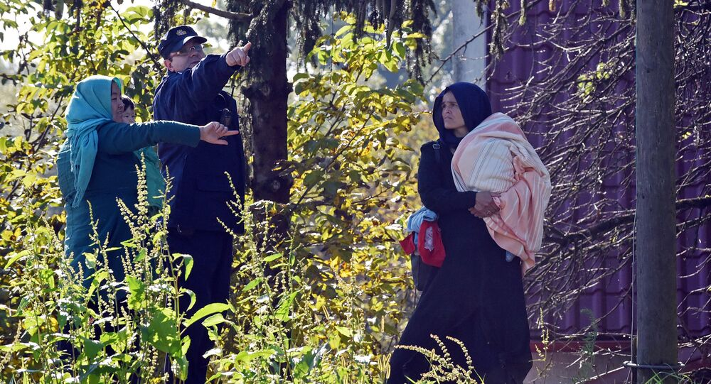 A Croatian police officer directs two women across the Sulta river as migrants and refugees travel across the Croatian-Slovenian border on October 20, 2015 near Kljuc Brdovecki