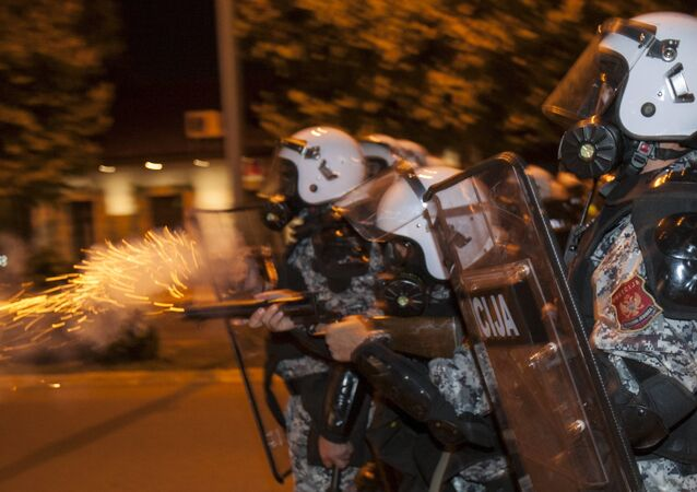 A riot policeman fires tear gas at protesters in front of the parliament building in Podgorica, Montenegro, October 24, 2015.