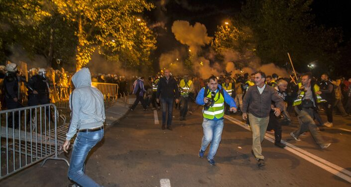 Protesters and journalists run from tear gas released by the police in front of the parliament building in Podgorica, Montenegro, October 24, 2015.