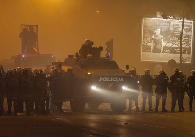 Riot police form a line with an armored vehicle during clashes with protesters in front of the parliament building in Podgorica, Montenegro, October 24, 2015.