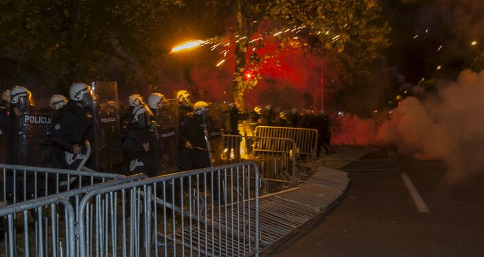 Demonstrators throw flares at police during protests in front of the parliament building in Podgorica, Montenegro, October 24, 2015.