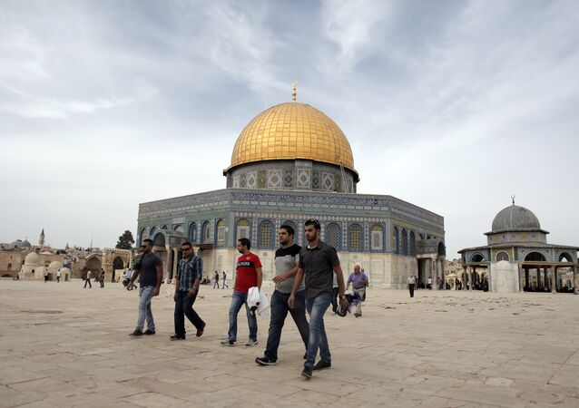 Palestinian men walk past the Dome of the Rock at the Al-Aqsa Mosque compound in Jerusalem before the Friday prayer, on October 23, 2015.