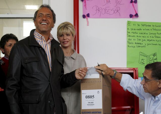 Presidential candidate Daniel Scioli of Front for Victory ruling party casts his vote next to his wife Karina Rabolini at a polling station in Buenos Aires, October 25, 2015.