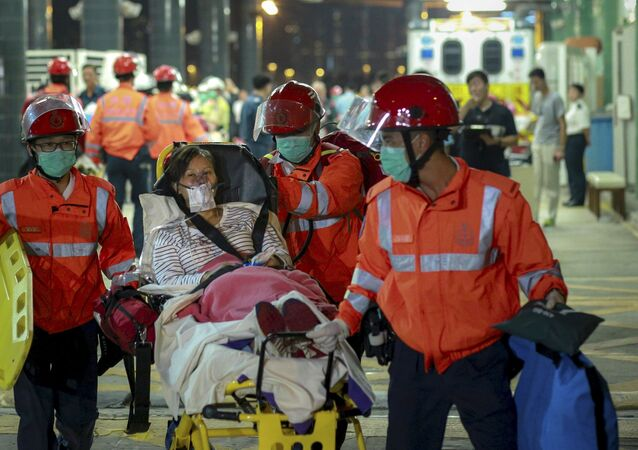 An injured ferry passenger is escorted by rescuers after getting onshore in Hong Kong, China October 25, 2015.