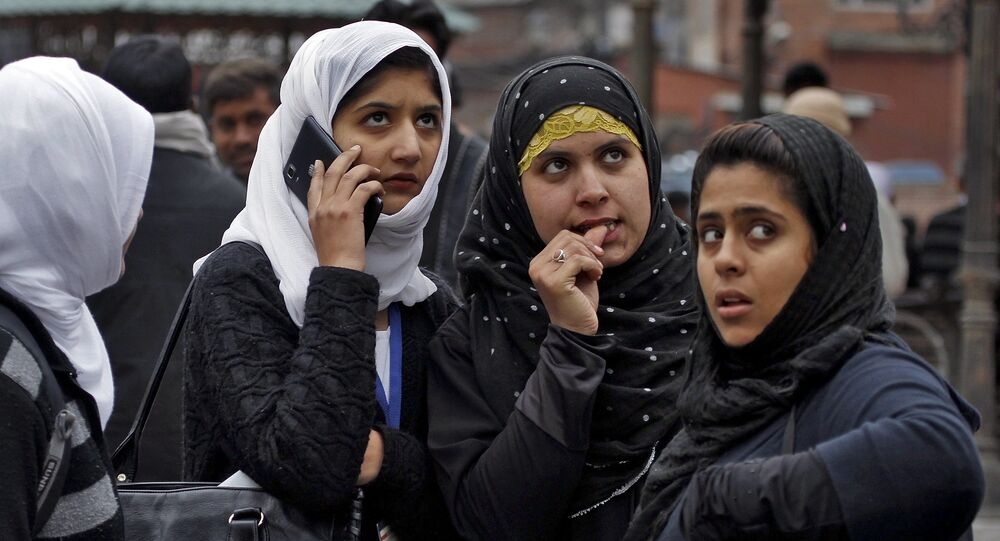 Kashmiri girls stand on a road divider after vacating their office buildings following an earthquake in Srinagar October 26, 2015.