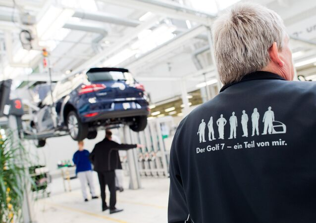 Employees of German car maker Volkswagen (VW) work on an electric car e-Golf at an assembly line at VW plant in Wolfsburg, central Germany, on October 21, 2015.