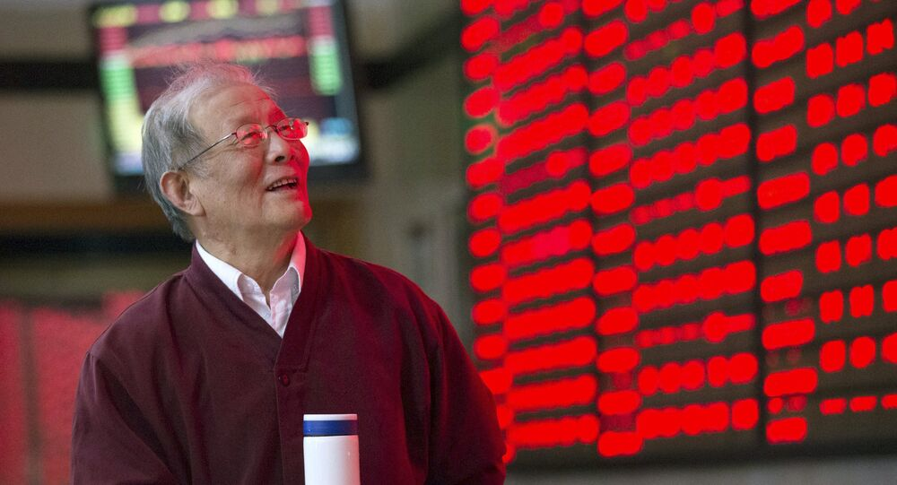 An investor looks at an electronic board showing stock information at a brokerage house in Nanjing, Jiangsu province, China, October 12, 2015.