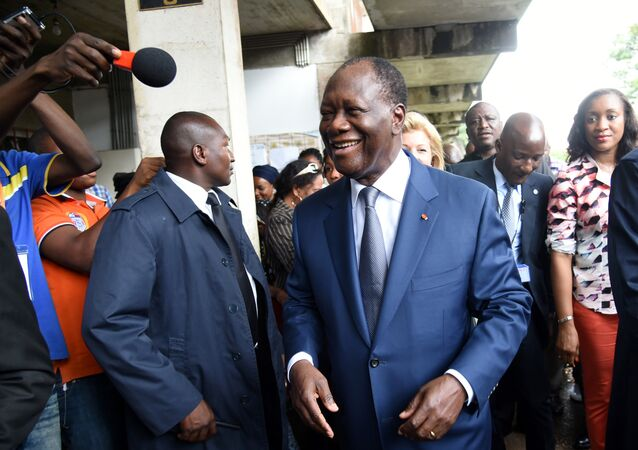 Incumbent Ivory Coast president Alassane Ouattara smiles to supporters as he leaves a polling station after voting in the Cocody residential district of Abidjan during Ivory Coast presidential elections