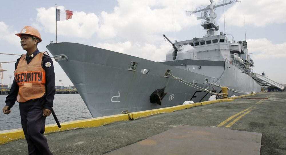 A Filipino security personnel keeps guard outside French surveillance frigate, Vendemiaire, as it docks at Manila's south harbor, Philippines on Wednesday March 18, 2009.