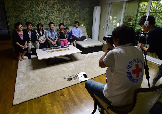 This photo taken on September 9, 2015 shows 72-year-old Ko Yong-Kyun (L-center), one of family members separated by the 1950-53 Korean War, posing with his family members during an interview by a Red Cross official at his home in Seoul