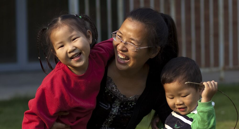 In this Monday, Oct. 17, 2011 photo, Wu Weiping, 35, plays with her daughter Wang Yile, 4, and her son Wu Yixiao, 2, near their home in Zhuji, in eastern China's Zhejiang province