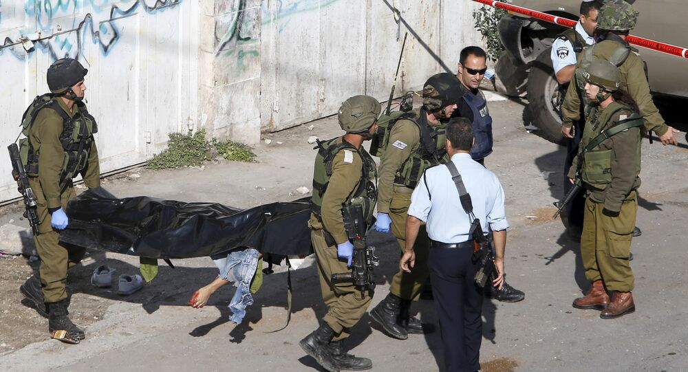 Israeli soldiers carry the body of a Palestinian, who Israeli police and army said stabbed a soldier, after he was shot by an Israeli policeman, in the West Bank old city of Hebron October 29, 2015