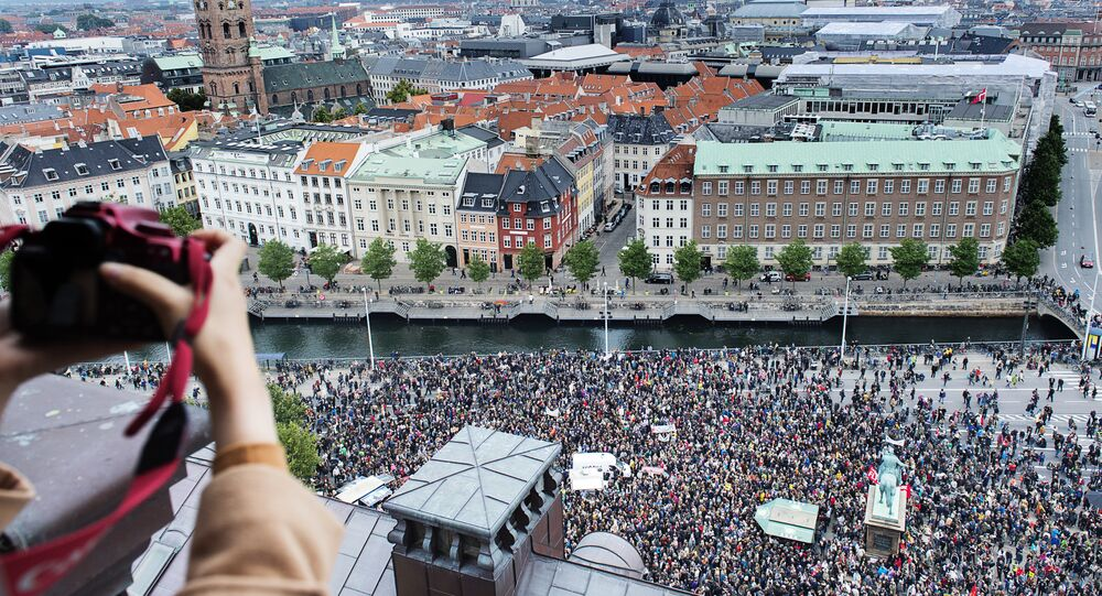 A photographer takes a photo of some 30,000 people who joined a rally in Copenhagen on September 12, 2015 in favour of taking in thousands of refugees seeking shelter in Europe, police said