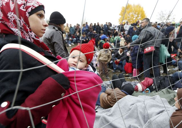 A woman holds a baby as migrants queue to cross the border into Spielfeld in Austria from the village of Sentilj, Slovenia, October 28, 2015.