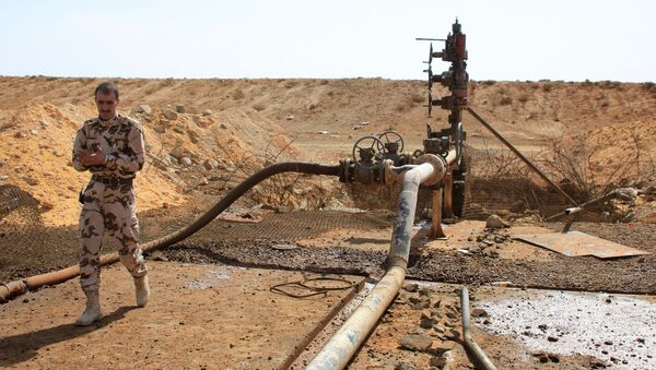 A member of the Syrian government forces walks next to a well at Jazel oil field, near the ancient city of Palmyra in the east of Homs province after they retook the area from Daesh. File photo - Sputnik International