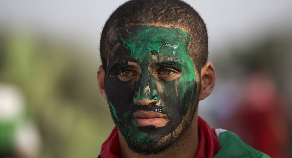 A Palestinain protester paints his face during clashes with Israeli solders during clashes at the Israeli border with Gaza east of Bureij refugee camp, central Gaza Strip, Friday, Oct. 23, 2015.